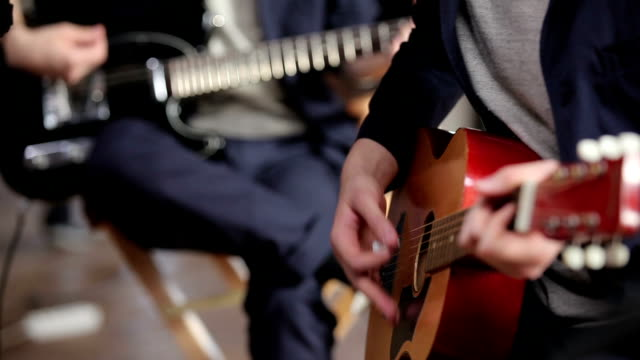Two unrecognizable guitarists in acoustic concert video