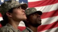 Two U.S. soldiers looking up in front of the flag video