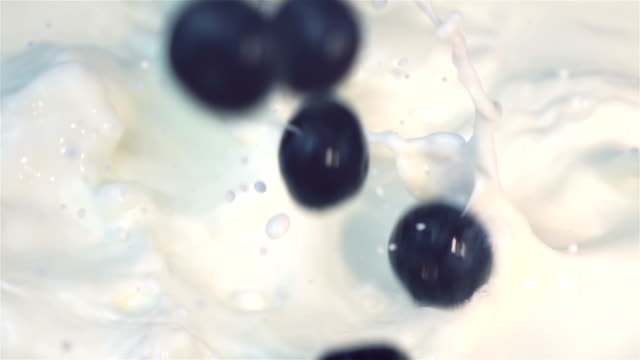 Two videos of blueberries falling into milk -real slow motion video