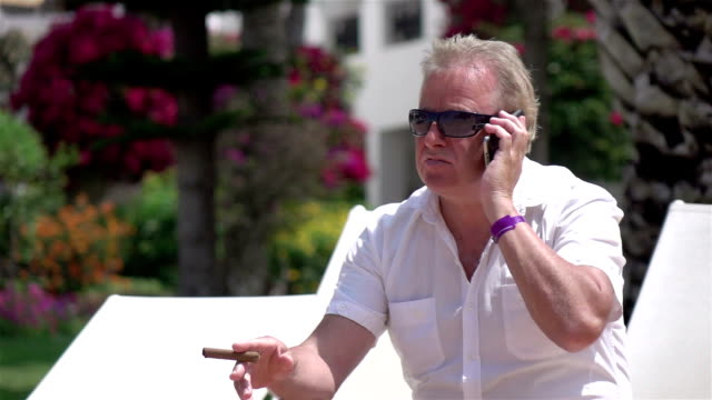 Two videos of businessman talking on the phone-real slow motion video