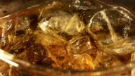 Two videos of cold cola with ice cubes in 4K video