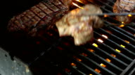 Two videos of flipping over steaks on the grill-slow motion video