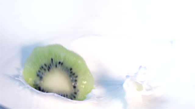 Two videos of kiwi falling into milk -real slow motion video