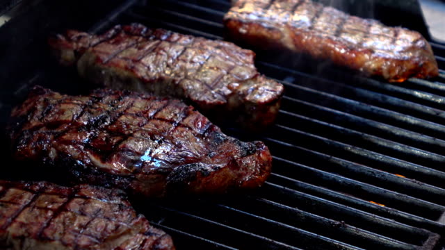 Two videos of opening the grill with steaks-real slow motion video