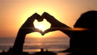 Two videos of symbol of love at the sunset-real slow motion video