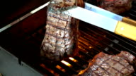 Two videos of turning over steaks on the grill-slow motion video