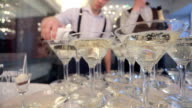Two waiters fill champagne pyramid of wineglasses on restaurant video