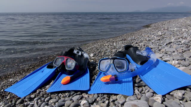 Two wet snorkeling sets fins scuba masks on wild pebble beach in summer video