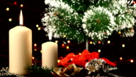 Two white candles with christmas decorations and tree on black, bokeh, light, garland, rotation video
