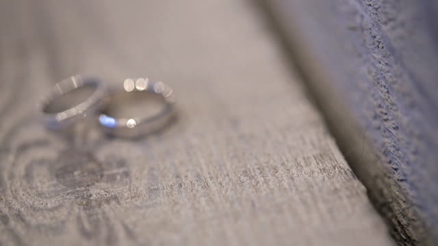 two white golden rings on photo shoot on wooden table outdoors video