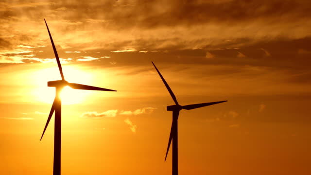 Two wind turbines turning at sunrise video