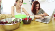 Two woman friends eat fruit and watch a laptop video