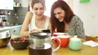 Two woman friends eat fruit and watch a smartphone video