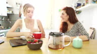 Two woman friends talking and drinking a tea video