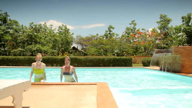 Two Woman Getting out of a Swimming Pool in Bikini video