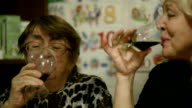 Two women clanging glasses. video
