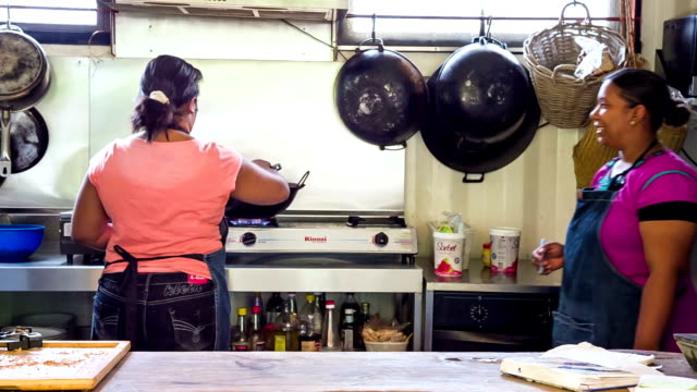 two women cooking in outdoor kitchen in mauritius video