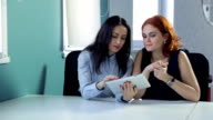 Two women discuss outfits on tablet during a break between work video