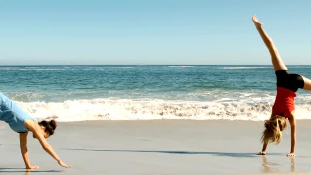 Two women doing cartwheels on the beach video
