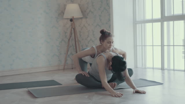 Two women doing yoga meditation and stretching exercises video