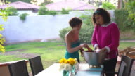 Two women filling a cooler with ice and beer video