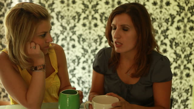 Two women having serious conversion over cup of coffee video