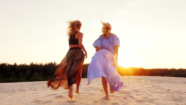 Two women in light dresses run toward the sun. Concept: women's dreams, health, happiness video