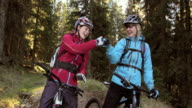 Two women on mountain bikes doing a fist bump in the forest video