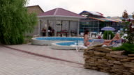 Two women relaxing by private swimming pool at summer vacation home video