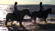 Two women ride on horse at river beach in water sunset light video