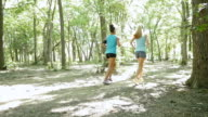 Two women running off road on dirt path in park video