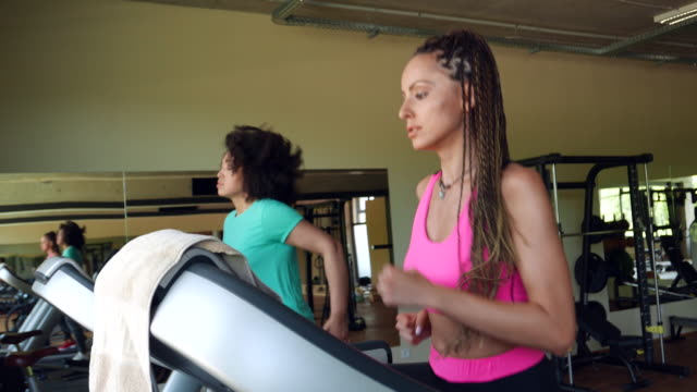 Two women running on treadmills in gym video