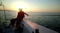 Two women sailing yacht, enjoying sea voyage, beautiful sunset, active video