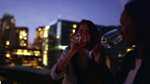 Two women sit at a table and have a glass of wine at a rooftop bar while laughing at sunset video