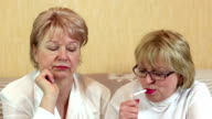Two women sits on a couch and one woman smokes a cigarette video