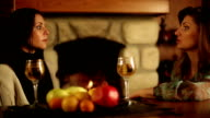 Two women sitting near fireplace and talking video