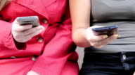 two women sitting nearby chatting on cell phones in unison video