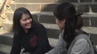 Two women sitting on the stairs, and chatting video