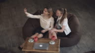 Two women take a photo selfie by smartphone video