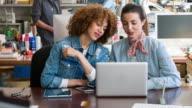 Two women using laptop in creative studio video