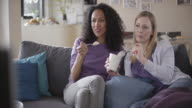 Two women watching a movie and eating ice cream video