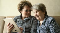 Two women watching photos on a digital tablet video