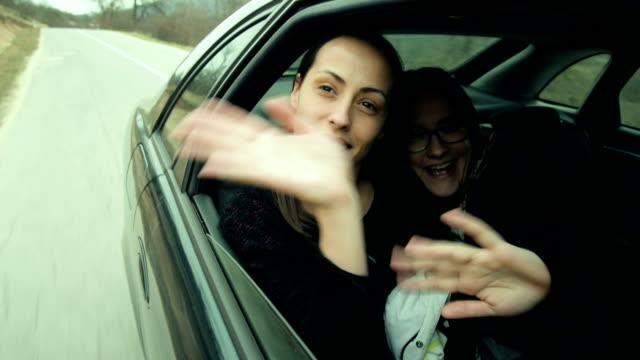 Two women waving in car video
