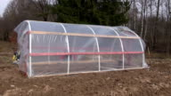 Two workers building polyethylene greenhouse video