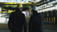 Two Workers Hard Hats Walking in Industrial Area with Cranes. video