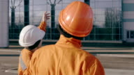 Two workers in orange uniform and helmet pointing at the building and examining the object. Slowmotion video