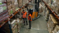 Two workers talking about the redistribution in the warehouse video