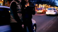 Two young adults in city play with tablet at night video