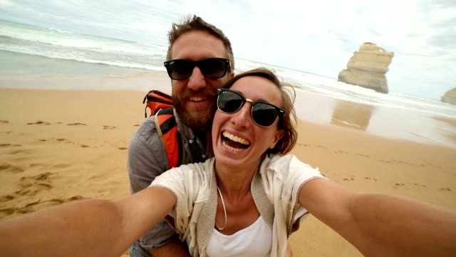 Two young adults take a selfie portrait on the beach video