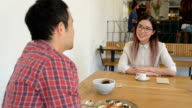 Two Young Asian Business People Meeting in Cafe video